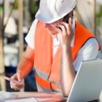 Trade construction worker in hi-vis jacket, helmet, on mobile phone using laptop