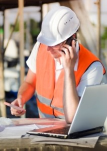 Trade construction worker in hi-vis jacket, helmet, on mobile phone using laptop