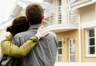 Homeowners satisfied with their new home improvement products; hug, yellow house, couple