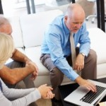 Sales and marketing executive selling to older couple on Apple computer